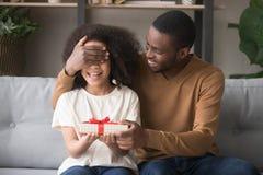 Gli occhi di amore della copertura del padre con la mano preparano per il regalo della figlia fotografie stock libere da diritti