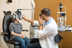 Gli occhi di Examining Preadolescent Boy dell'optometrista immagine stock