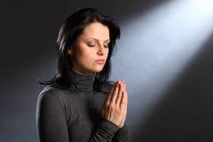 Gli occhi di momento di religione hanno chiuso la giovane donna nella preghiera Fotografie Stock Libere da Diritti