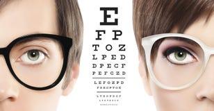 Gli occhi e gli occhiali si chiudono su sul grafico di prova visivo, vista e immagine stock