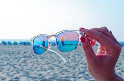 Gli occhiali da sole con l'hotel Neptun nel nde del ¼ di Warnemà nei precedenti sulla spiaggia nel sole hanno tenuto da una mano fotografia stock