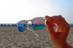 Gli occhiali da sole con l'hotel Neptun nel nde del ¼ di Warnemà nei precedenti sulla spiaggia nel sole hanno tenuto da una mano fotografia stock libera da diritti