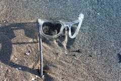 Gli occhiali da sole curvati e rovinati di sport hanno andato su una spiaggia al sole immagine stock libera da diritti
