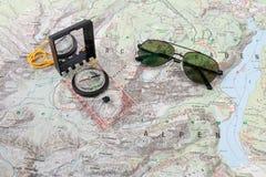 Gli occhiali da sole del pilota e della bussola su un'escursione tracciano Fotografia Stock