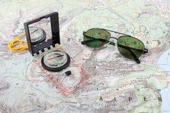 Gli occhiali da sole del pilota e della bussola su un'escursione tracciano Immagini Stock Libere da Diritti