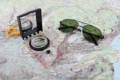 Gli occhiali da sole del pilota e della bussola su un'escursione tracciano Immagini Stock
