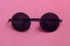Gli occhiali da sole neri alla moda con i vetri rotondi si trova su una coperta fatta del tessuto rosa-chiaro molle e lanuginoso  immagini stock libere da diritti