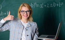 Gli occhiali di usura di donna tengono Internet praticante il surfing del computer portatile Grande risorsa per gli insegnanti Co immagine stock