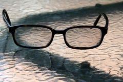 Gli occhiali sono sulla tavola per dare ai miei occhi un resto Fotografia Stock Libera da Diritti