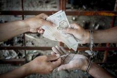 Gli offensori danno i soldi in cambio del rilascio, fotografia stock