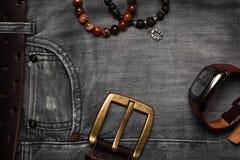 Gli oggetti di vita di tutti i giorni, jeans degli uomini, cinghia, orologio, braccialetti a disposizione Vista superiore piana M Immagine Stock Libera da Diritti