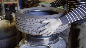 Gli oli del meccanico di automobile dell'uomo stancano la superficie sulla ruota nell'esterno di servizio di riparazione automati archivi video