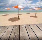 Gli ombrelli sulla spiaggia e svuotano la tavola di legno della piattaforma. Immagini Stock