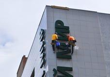 Gli operai puliscono le lettere su una costruzione Fotografia Stock