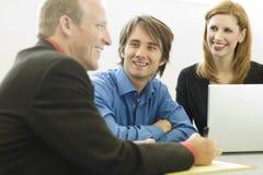 Gli operai si siedono e comunicano Immagine Stock