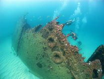 Gli operatori subacquei di scuba esplorano un naufragio nell'Oceano Indiano fotografia stock