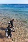 Gli operatori subacquei entrano nel mare. Fotografia Stock