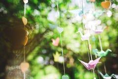 Gli origami crane, uccelli di carta sul fondo del bokeh Fotografie Stock