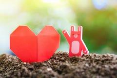 Gli origami di carta rossi del cuore con coniglio giocano sul suolo contro sfuocatura fotografia stock