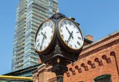 Gli orologi classici d'annata che stanno contro la costruzione di mattone al distretto storico della distilleria di Toronto quadr fotografia stock