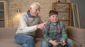 Gli orologi del nonno come il nipote gioca il videogioco L'uomo anziano sta sedendosi sullo strato con un giovane ragazzo grasso archivi video