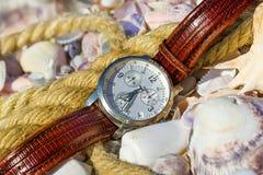 Gli orologi del ` s degli uomini si trovano sulla spiaggia Fotografia Stock