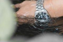 Gli orologi, orologi, impermeabili, orologio del metallo è cadenti e spruzzanti nella chiara acqua, subacquea a disposizione fotografie stock libere da diritti