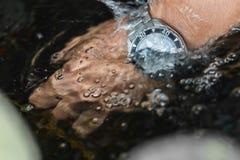 Gli orologi, orologi, impermeabili, orologio del metallo è cadenti e spruzzanti nella chiara acqua, subacquea a disposizione fotografie stock