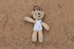 Gli orsacchiotti anziani sono stati lasciati da solo nella sabbia, giocattoli che nessuno era interessato dentro immagini stock