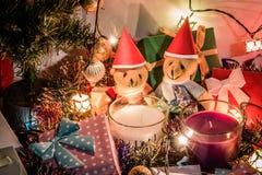 Gli orsacchiotti di una coppia, la candela bianca e viola di natale e l'ornamento decorano il Buon Natale ed il buon anno Fotografia Stock