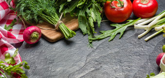 Gli ortaggi freschi ed i verdi nei mazzi hanno sistemato nel telaio su un fondo di pietra nero Fotografie Stock Libere da Diritti