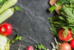 Gli ortaggi freschi ed i verdi nei mazzi hanno sistemato nel telaio su un fondo di pietra nero Fotografia Stock
