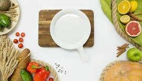 Gli ortaggi freschi, la frutta ed il piatto rotondo anneriscono il tagliere su fondo bianco, vista superiore Fotografia Stock Libera da Diritti