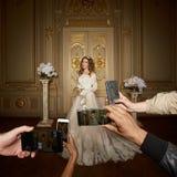 Gli ospiti prendono le fotografie della sposa sugli smartphones Fuoco sugli smartphones fotografia stock