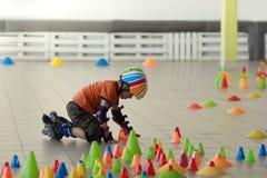 Gli ostacoli della costruzione del ragazzo con i pioli imparare il rollerskate di slalom inganna immagini stock