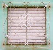 Gli otturatori bianchi chiusi sulla finestra dietro metallo bianco grigliano sulla dissolvenza Immagine Stock Libera da Diritti