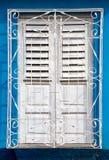 Gli otturatori bianchi recentemente dipinti sulla finestra dietro metallo bianco grigliano Fotografia Stock
