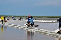 gli Sale-operai nella mascherina trasportano il sale sulla loro spalla Fotografia Stock