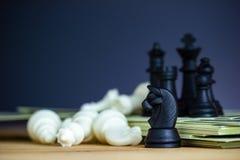 Gli scacchi neri stanno sopra le banconote del dollaro fotografie stock libere da diritti