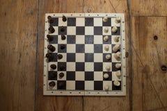 Gli scacchi su un bordo di legno hanno messo su un certo pavimento di legno Immagine Stock