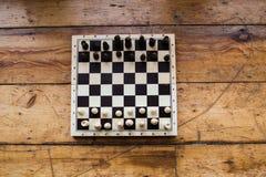Gli scacchi su un bordo di legno hanno messo su un certo pavimento di legno Immagini Stock Libere da Diritti