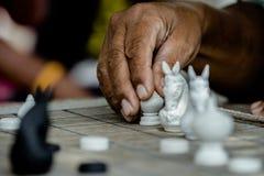Gli scacchi tailandesi commoventi della mano dell'uomo anziano dipendono la scacchiera di legno Fotografie Stock Libere da Diritti