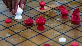 Gli scacchi tailandesi commoventi della mano dell'uomo anziano dipendono la scacchiera di legno Fotografia Stock