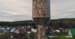 Gli scalatori industriali dipingono la torre del ferro Job rischioso Lavoro estremo Alpinista del lavoratore stock footage