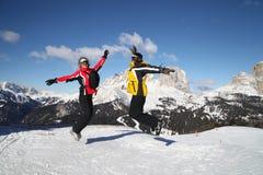Gli sciatori che saltano ad una cima della montagna Fotografia Stock