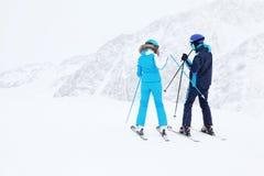 Gli sciatori dell'uomo e della donna preparano per il pendio Fotografia Stock
