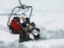 Gli sciatori e gli snowboarders sono su un ascensore di sci (seggiovia) Fotografie Stock