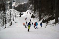 Gli sciatori e gli snowboarders che guidano su uno sci pendono Immagine Stock Libera da Diritti
