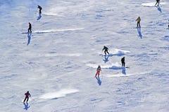 Gli sciatori e gli snowboarders che guidano su uno sci pendono Fotografie Stock Libere da Diritti