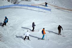 Gli sciatori e gli snowboarders che guidano su uno sci pendono Fotografia Stock